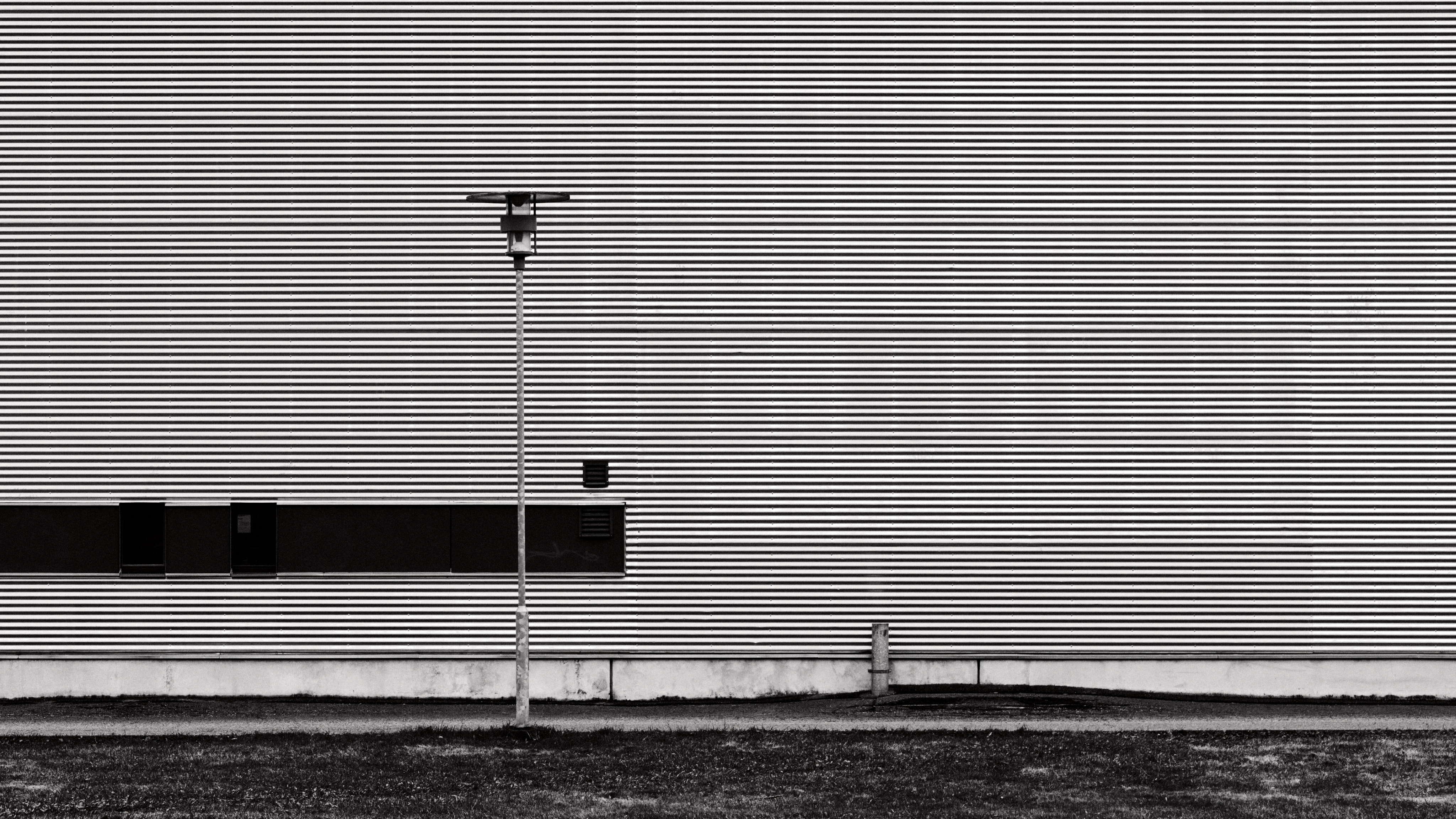 a more abstract photo. extremely repetitive texture on a massive wall - it's basically bent sheet metal - and a couple of details. a lamppost on the left, some sort of a pipe on the right, and possibly air vents with a darker background on the left.